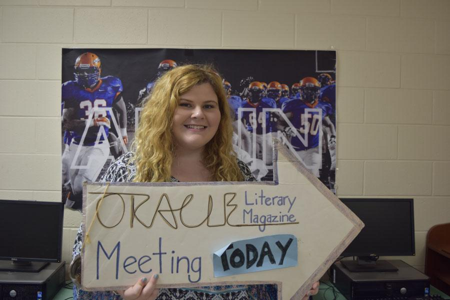 Oracle editor Madison Murphy proudly holds the sign that indicates Monday meetings.
