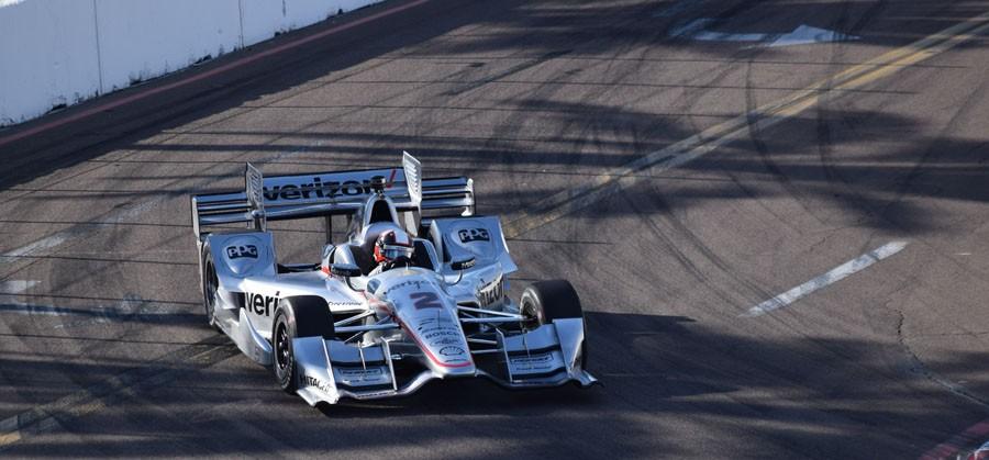 During practice day, Juan Pablo Montoya makes a turn around Dan Wheldon Way.