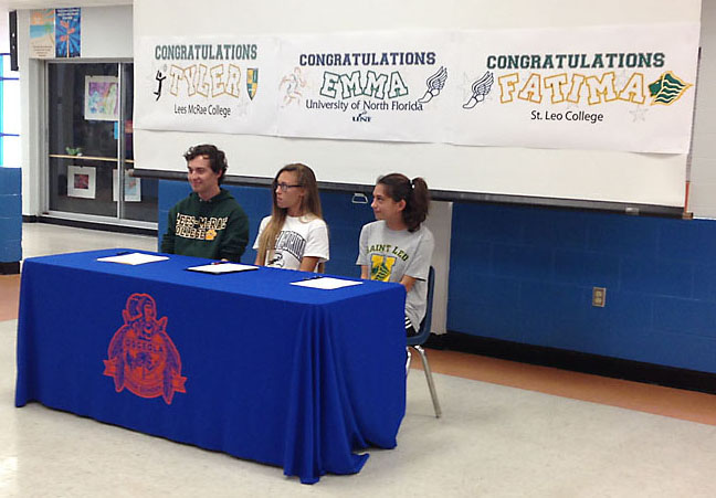 Tyler+Doyle%2C+Emma+Grantges+and+Fatima+Abu-Rumman+prepare+to+sign+with+three+different+colleges.