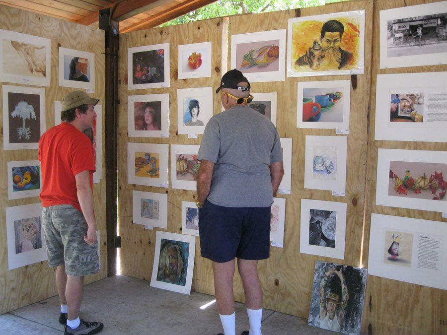 Art+teacher+Mr.+LoCascio+explains+his+students%27+art+works+to+a+visitor+who+stopped+by+the+Osceola+booth.