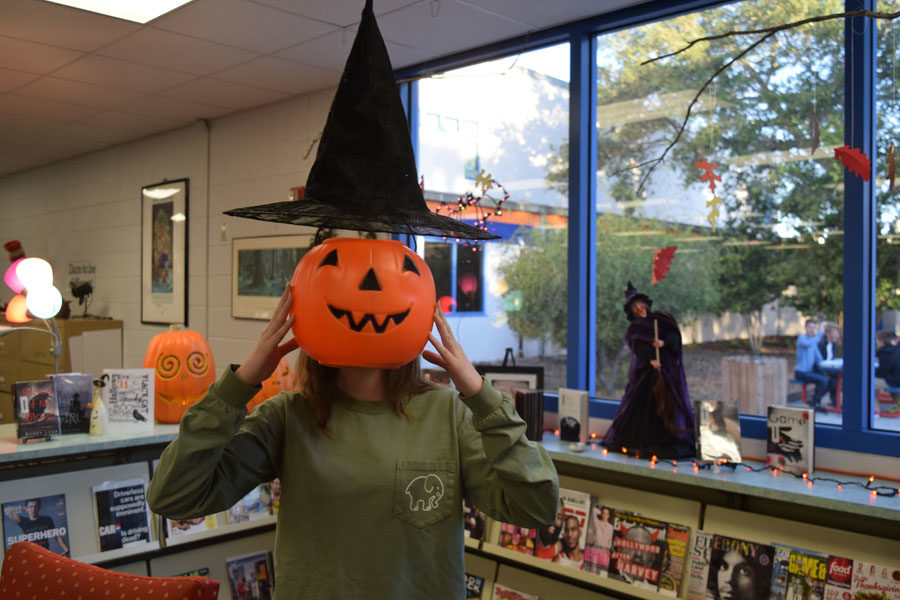 Tiffany+Jette%2C+12th+grade%2C+has+fun+with+decorations+in+the+library+for+a+spooky+Halloween+picture.