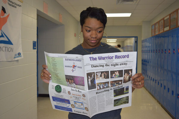 Amari Williams shows off the latest edition of the school newspaper.