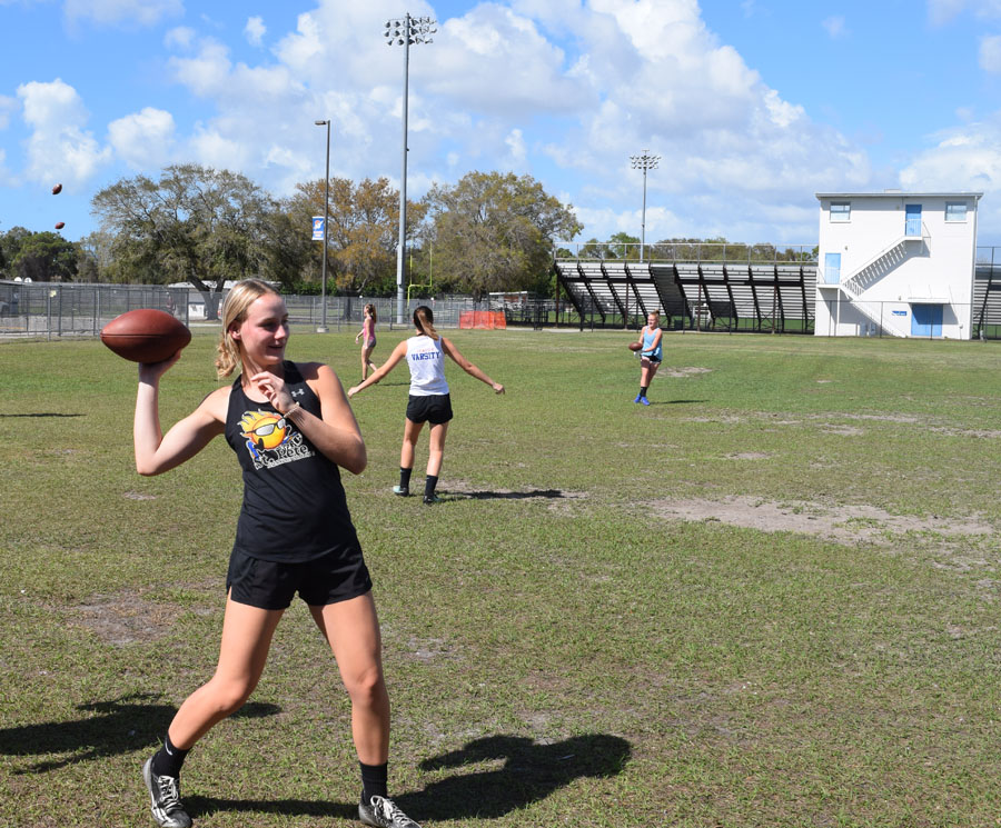 Grace Thrower throws a football to teammates.
