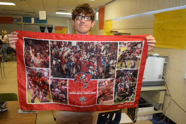Ethan Tuttle holds up the Bucs Super Bowl flag from 2003.